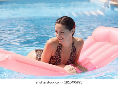 Woman on pink inflatable in swimming pool wearing swimming suit with leopard print, looking smiling aside, spending summer vacation on luxury resort.