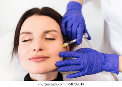 A woman on the procedure of injections in a cosmetology clinic