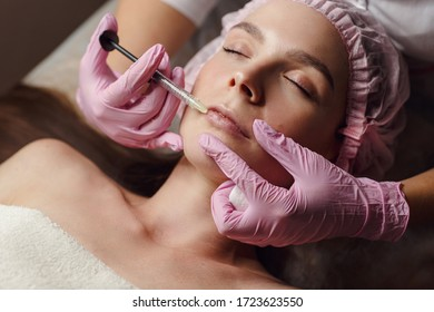 Woman on rejuvenation procedure in beauty clinic filler injection. She lying calmly at clinic. The expert beautician in pink gloves is filling female wrinkles by hyaluronic acid. Injection of beauty.