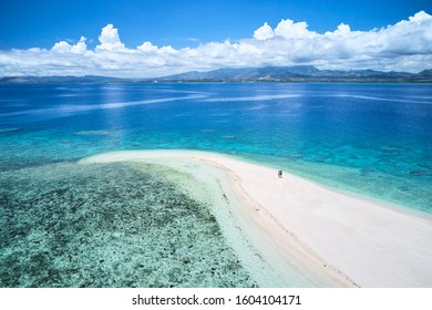 Woman on remote island in Fiji overlooking blue coral reef