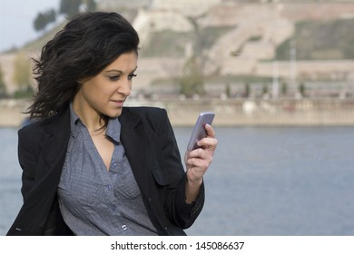Woman on the river bank with your mobile phone,