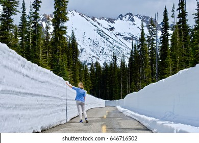 Woman  on the road with snow walls. North Cascades National Park. Bellingham. Seattle. Cascade mountains. Washington. The United States.