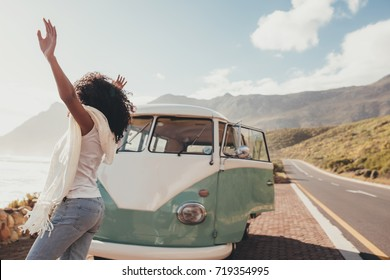Woman on roadtrip standing outdoors on countryside road near a mini van. Female having fun on vacation.