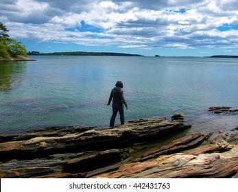 Woman on rocky shore of Casco Bay, Cape Elizabeth, Maine.