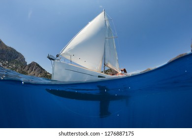 Woman on sailing yacht floating on the sea against the background of cliffs and beach. Sunny is a quiet day.