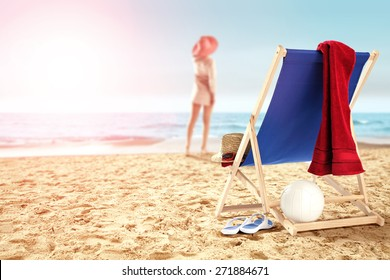 woman on sand chair with red towel and ball