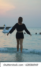 Woman on sandy beach in sunset leaving
