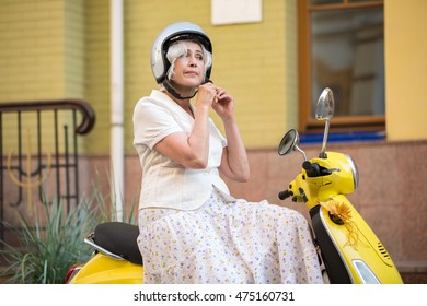 Woman on scooter wearing helmet. Bright yellow scooter. Safety first of all. Serious attitude to rules.
