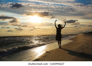 Woman on the sea coast on sunset