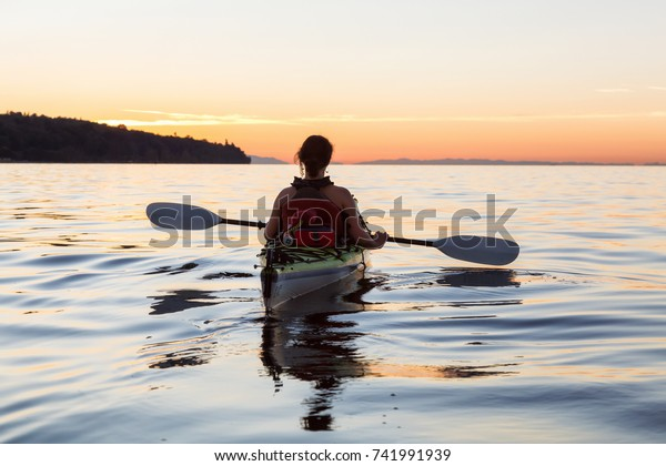Woman on a sea kayak is paddling in the ocean during a colorful and vibrant sunset. Taken in Jericho, Vancouver, British Columbia, Canada.
