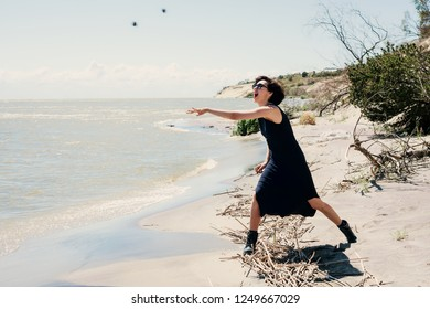 Woman on the sea throws stones into the water
