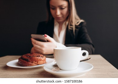 a woman on the second plan writing on the phone in the cafe with coffee and cake on the table