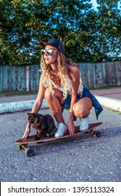 Woman on skate, cat pet pussy, summer in city, background fence road. Denim baseball cap long hair. The concept of fashion style, lifestyle of youth. Rest at the weekend in nature in spring.