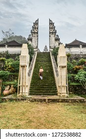 Woman on stairs to the entrance to the Pura Lempuyang temple on Bali, Indonesia
