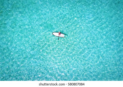 Woman on a stand up paddle boat over turquoise waters