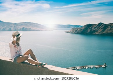 Woman on summer vacation watching beautiful sunset over sea.