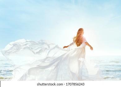 Frau am sonnigen Strand in weißem, flatterndem Kleid, Modemodell Zurhinten Ansicht, Seidenbekleidung auf Wind