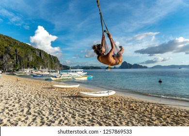 A woman on a swing at the 7 Commandos island beach, El nido, Palawan, Philippines