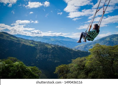 Woman on the swing of the end of the world in Baños, Ambato. The tree house, Ecuador, Latin America