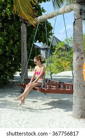 Woman on a swing at the sea;