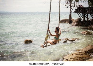 woman on swing at sea shore, tropical holidays