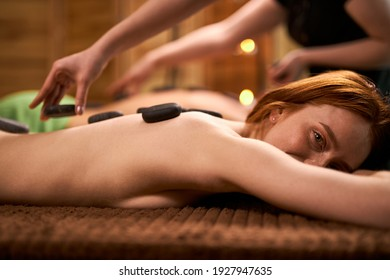 woman on table takes spa stone massage, spa concept. In spa center, taking care of health and beauty. side view