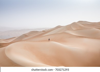 woman on top of a dune in Rub al Khali Desert at the Empty Quarter, in Abu Dhabi, United Arab Emirates