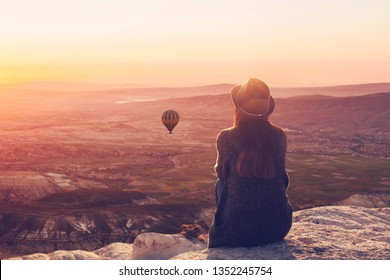 A woman on top of a hill alone admires the tranquil natural landscape and balloon and enjoys silence in Cappadocia in Turkey