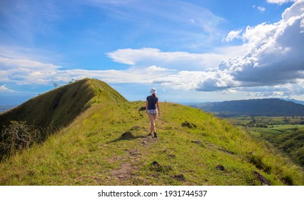 Woman on the top of hill on natural mountain landscape. Tourist travels through the mountains. Photos of holidays in beautiful places. Tracker conquers mountain peaks. Outdoor activities.