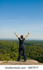 Woman on the top of a mountain happy