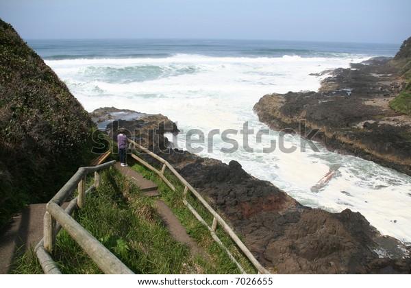 Woman on trail to Devil's Churn, surf action,Cape Perpetua,Oregon coast