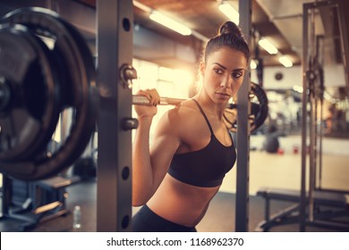 Woman on training with barbell in fitness center