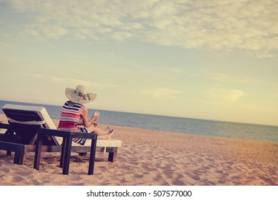 Woman on a tropical beach holiday. Luxury wooden lounge and sunny outdoors background