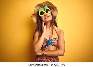 Woman on vacation wearing bikini and pineapple sunglasses over isolated yellow background with hand on chin thinking about question, pensive expression. Smiling with thoughtful face. Doubt concept.