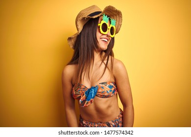 Woman on vacation wearing bikini and pineapple sunglasses over isolated yellow background looking away to side with smile on face, natural expression. Laughing confident.