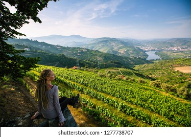 Woman on the viewing point of Douro Valley, Portugal. Top view of river, and the vineyards are on a hills.