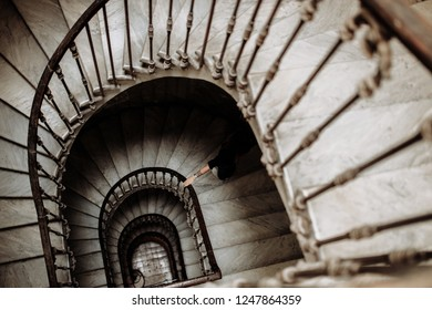 Woman on vintage ladder. Spiral staircase