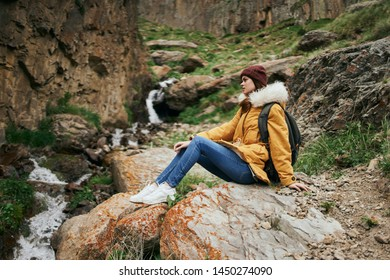 woman on a waterfall in the mountains nature trip tour
