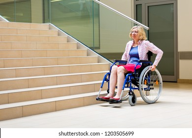 woman on wheelchair standing before stairs looking up for help