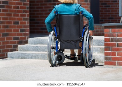 woman on wheelchair standing before stairs and waiting for help
