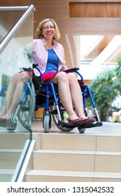 woman on wheelchair standing just before steps down and smiling