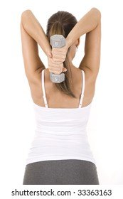 Woman on white holding silver dumbbells doing tricep extensions.