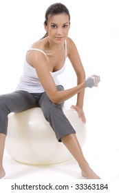 Woman on white holding silver dumbbells on a ball