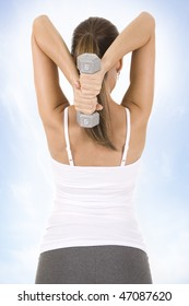 Woman on white holding silver dumbbells to camera.