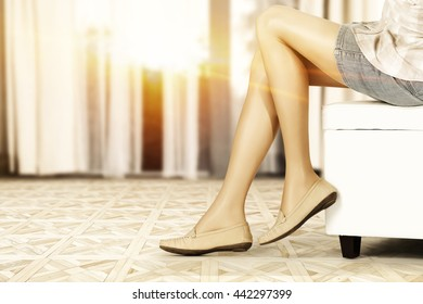 woman on white sofa and woman legs and brown shoes