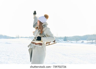 Woman on winter holiday holding her ice-skates