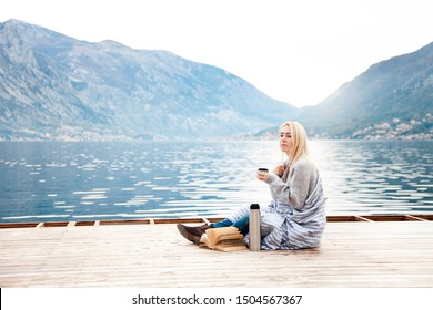 Woman on wooden pier by winter sea, mountains. Cozy picnic with coffee, hot beverages, tea or cocoa in thermos and mug, warm plaid, opened book. Girl is enjoying nature, wellbeing, reading on beach