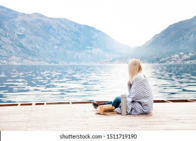 Woman on wooden pier by winter sea, mountains. Cozy picnic with coffee, hot beverages, tea in thermos and mug, warm plaid, opened book. Girl is enjoying nature, relaxation, reading on beach