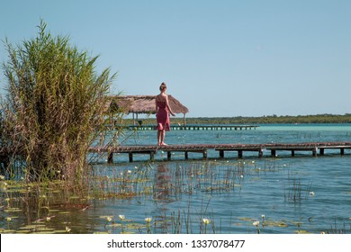 Woman on the wooden pier in the lagoon of Bacalar (lagoon of the seven colors),Quintana roo , Mexico
