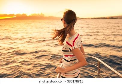 Woman on a yacht enjoying the beautiful sunset.